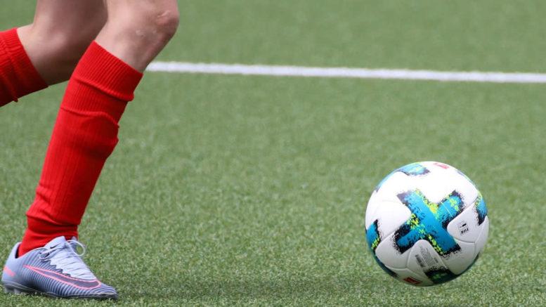 Youth kicking football